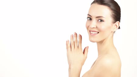 rosto humano : Attractive young woman smiling and holding her hands around her face and neck in a beauty style pose