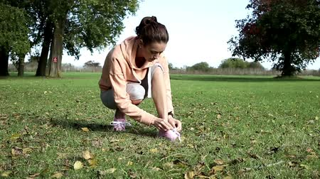 tying : Young woman tying her shoelaces before going on a run