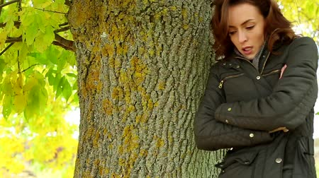 cold : Beautiful young woman leaning against a tree on a bright Autumn day relaxing