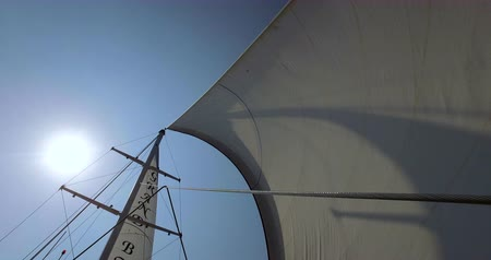 lanoví : Large yacht sail blowing in the wind on a blue sky day