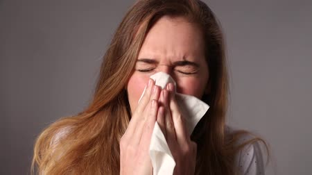 üfleme : sick young woman sneezing, blowing her nose with a tissue paper for cold or itchy pollen allergies in the winter or springtime season, gray background studio Stok Video