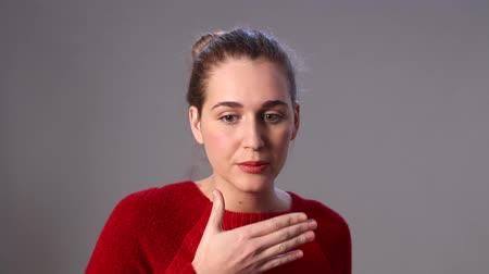 surprised : expressive beautiful young woman covering her mouth for a reaction to mistake, embarrassment, surprised with body language and hand gesture, gray background