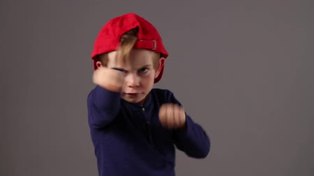 bojování : violent young child with red hat back and freckles fighting with his hands and fists, threatening or defending himself at preschool, grey background studio