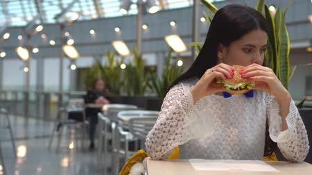 hambúrguer : Young woman eating fast food, hamburger in cafe Vídeos