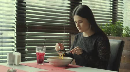 garfos : The young woman eats spaggeta paste in cafe. The lonely girl eats at restaurant.