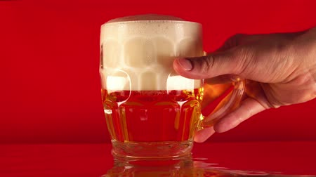 cseppfolyósítás : the hand takes a glass of beer. Red background.
