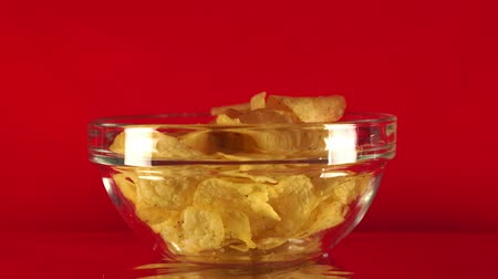 engorda : Potato chips in free fall in a cup. The hand takes a cup with chips