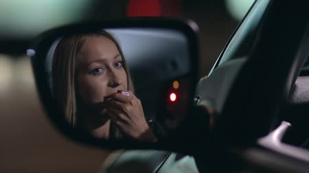 ruj : Young woman applying red lipstick in the car