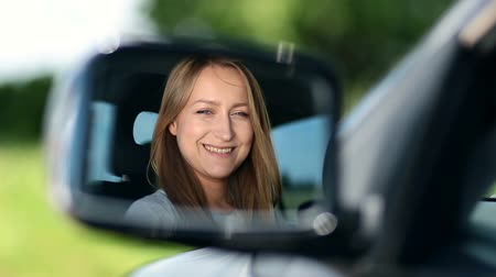 utazó : Young woman driver looking at car side view mirror