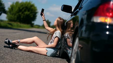 sorunlar : Blonde girl sitting on road near her broken car Stok Video