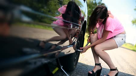 pneus : Attractive girl trying to remove wheel with wrench
