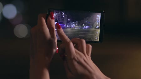 make photo : Woman takes photo of city in streetlights at night