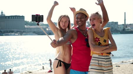 vara : Group of smiling friends making selfie on beach