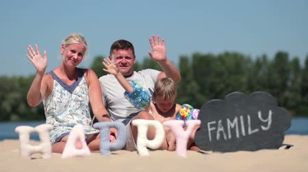 olá : Happy family sitting on the beach and waving hello