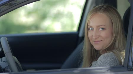 řidič : Smiling female driver opening car window