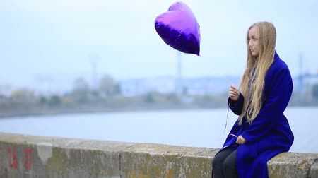 cobalt : Beautiful sad blond woman with violet balloon