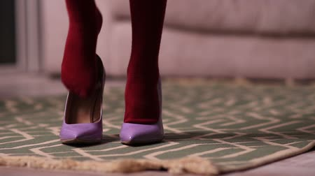 calçados : Little girl putting on mothers shoes on the floor Stock Footage