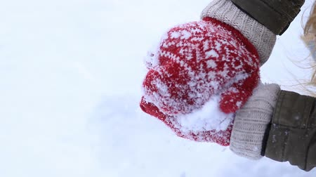 mittens : Female hands in knitted mittens making snowball