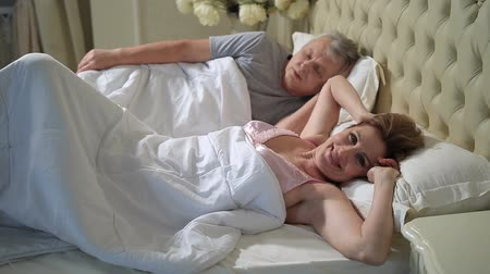 amadurecer : Senior woman in bed stretching and waking up