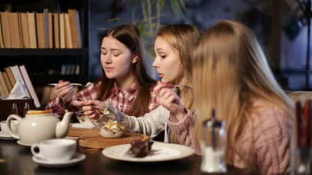 coffee time : Two young teenage girls eating desserts in cafe