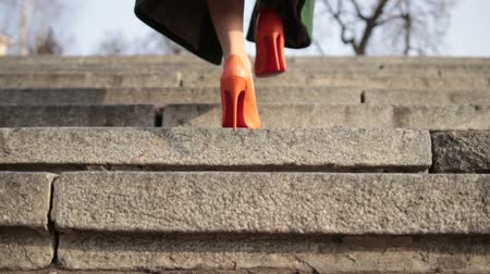 step by step : Female legs walking upstairs on stone staircase