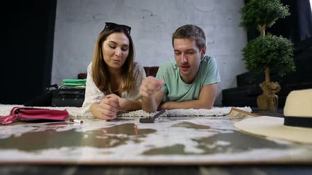 rajzszeg : Hipster couple placing pins on scratch travel map Stock mozgókép