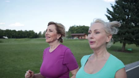hareketli : Two pretty senior females joggers training in park Stok Video