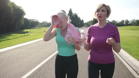 aktivní : Fitness senior women drinking water after jogging