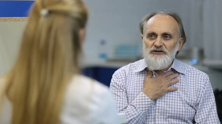 complaints : Male senior patient visiting a doctor at hospital Stock Footage