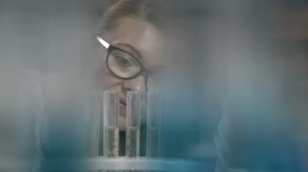 ученый : Female scientist examining test tube in lab