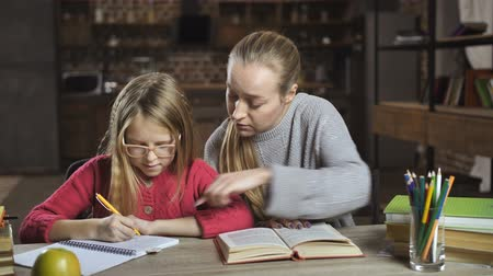 gimnazjum : Mother helping her daughter with homework at home