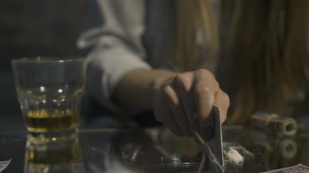 snorting : Middle section of female making cocaine line on table Stock Footage