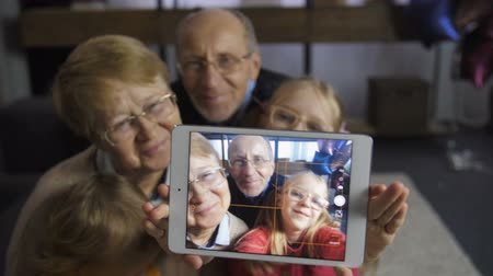 obrázky : Girl taking selfie with grandparents on touchpad