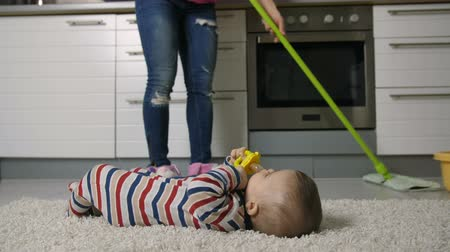 házimunkát : Close-up of female legs mopping floor with baby