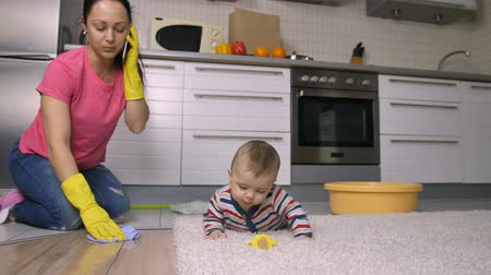 házimunkát : Working mom doing housework while caring baby