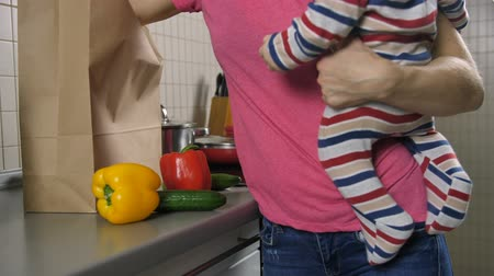 házimunkát : Moms midsection with baby unloading groceries