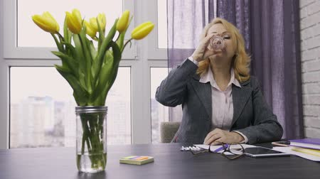 annoyance : Senior woman taking pills from headache at office