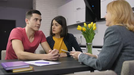 ипотека : Young couple talking to agent about mortgage