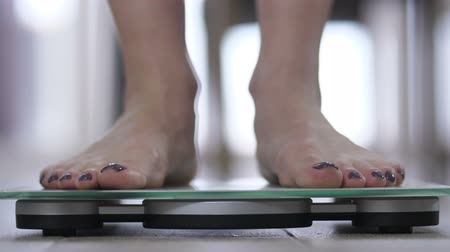 weighing machine : Womans feets standing on body weight scales Stock Footage