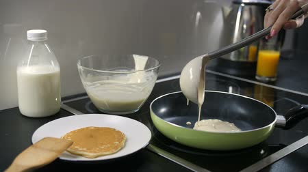 induction cooker : Hand pouring pancake batter into the pan
