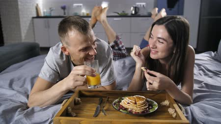 креп : Cheerful couple eating breakfast pancakes in bed