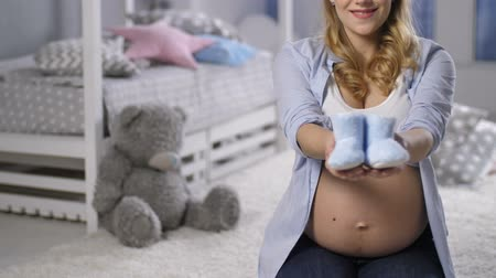 booties : Pregnant woman showing baby booties to camera