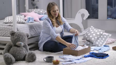 bekleyen : Pregnant mom taking out baby clothes from gift box Stok Video