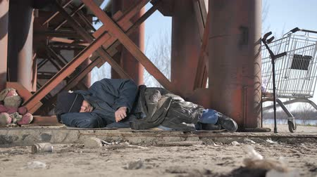hajléktalan : Cold homeless beggar sleeping under bridge