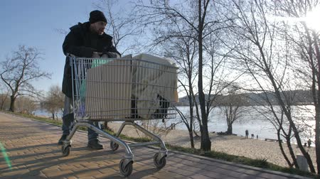 ghetto streets : Front view of homeless mature man pushing cart