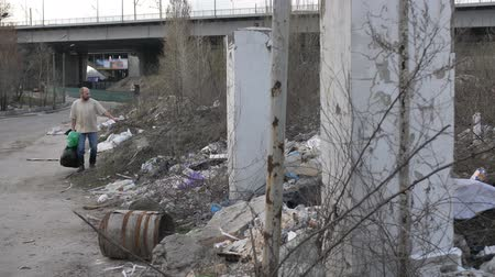 újrahasznosított : Man looking for plastic at garbage dump in city Stock mozgókép