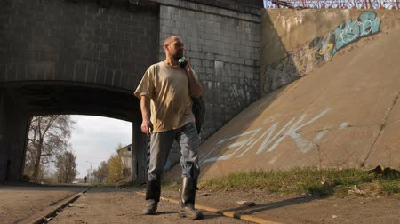 ghetto streets : Homeless mature man walking near bridge