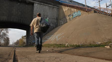 ghetto streets : Back view of homeless man walking in city