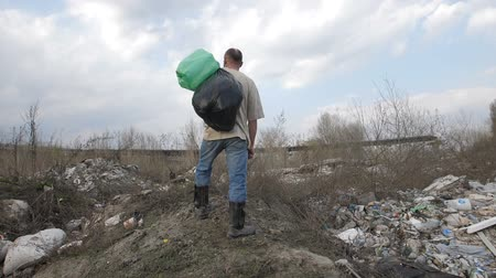 grãos : Homeless man standing on garbage hill at dump site