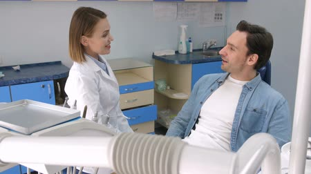 lab employee : Female dentist greeting male patient at clinic
